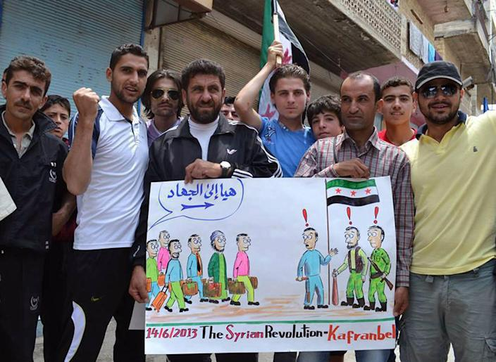 """In this citizen journalism image provided by Edlib News Network (ENN), anti-Syrian regime protesters hold a placard with a caricature during a demonstration at Kafr Nabil town in Idlib province, northern Syria, June 14, 2013. The Syrian government on Friday dismissed U.S. charges that it used chemical weapons as """"full of lies,"""" accusing President Barack Obama of resorting to fabrications to justify his decision to arm Syrian rebels. The commander of the main rebel umbrella group welcomed the U.S. move. The Arabic on the placard reads, """"Let's go to Jihad."""" (AP Photo/Edlib News Network ENN)"""