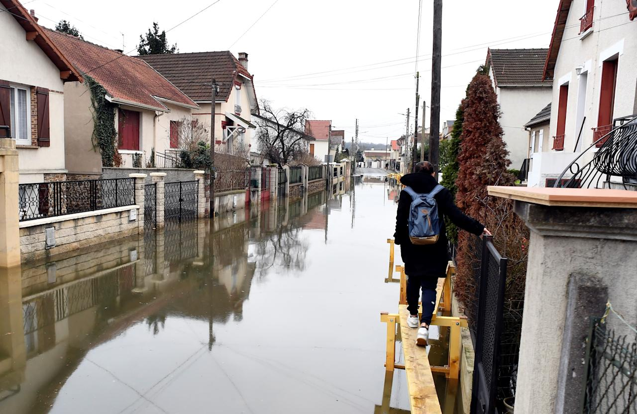 <p>A woman walks on a makeshit elevated track set to help inhabitants reach their home in a flooded street on Jan. 30, 2018, in Villeneuve-Saint-Georges, near Paris. (Photo: Alain Jocard/AFP/Getty Images) </p>