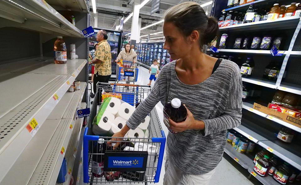 <p>Erica McMillan stocks up with what's left on the shelves at Walmart in Oahu, Hawaii on Aug. 22, 2018, in preparation for the arrival of Hurricane Lane. (Photo: Ronen Zilberman/AFP/Getty Images) </p>