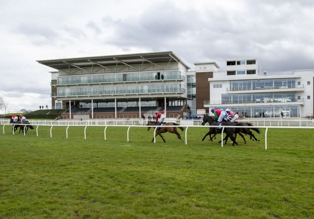 Runners and riders pass the empty stands at a race meeting at Wetherby on Tuesday (Alan Wright/Handout)