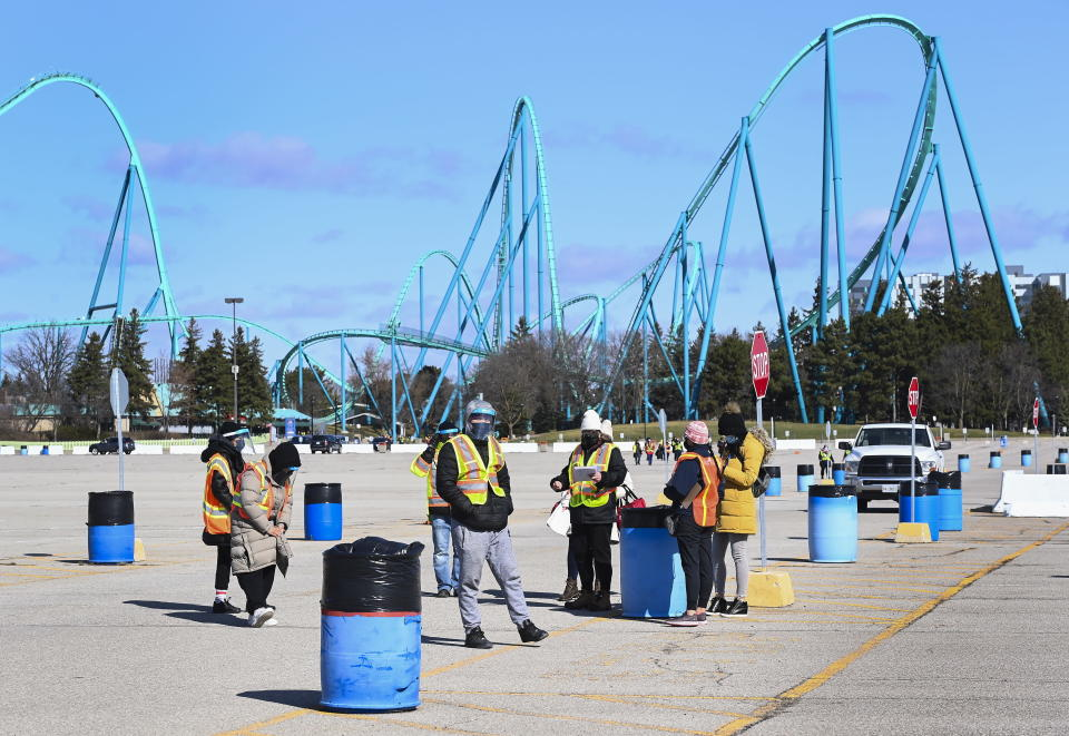Health care workers prepare to take patients at a drive-thru COVID-19 mass vaccination site at Canada's Wonderland in Vaughan, Ontario, Monday, March 29, 2021. (Nathan Denette/The Canadian Press via AP)