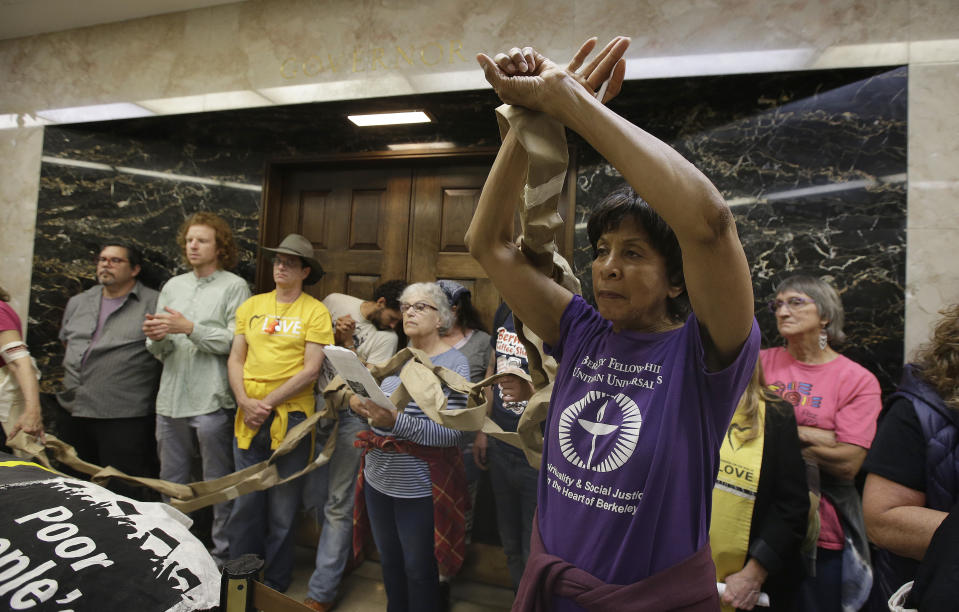 Virginia Hollins-Davidson , right, join other protesters blocking the door to the governor's office during a protest by the Poor People's Campaign at the Capitol, Monday, June 18, 2018, in Sacramento, Calif. The group has been advocating for a variety of causes, including reducing income inequality, preserving the environment and improving health care for the poor. (AP Photo/Rich Pedroncelli)