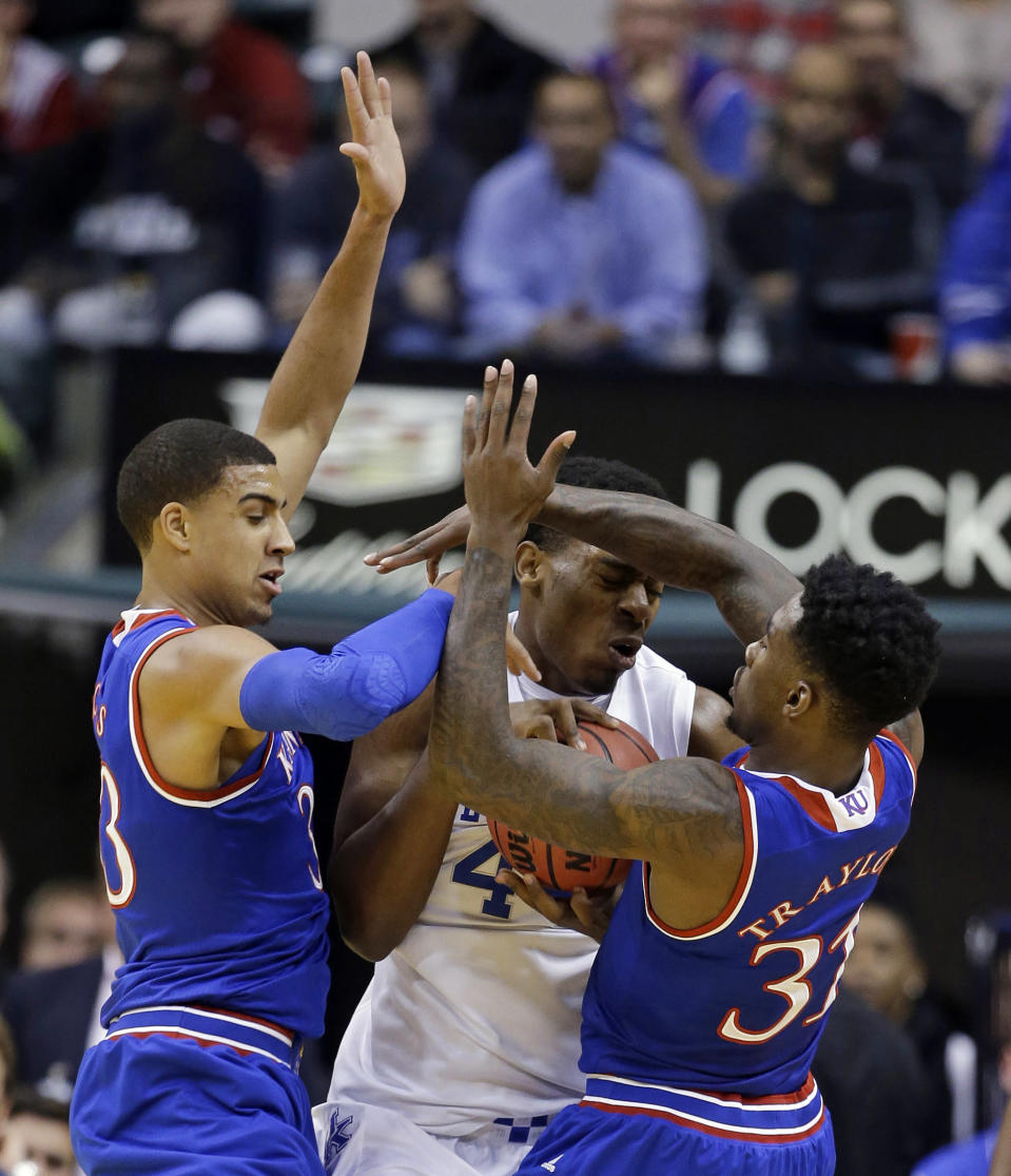 Kentucky's Dakari Johnson, center, is defended by Kansas's Landen Lucas, left, and Jamari Traylor during the first half of an NCAA college basketball game Tuesday, Nov. 18, 2014, in Indianapolis. (AP Photo/Darron Cummings)