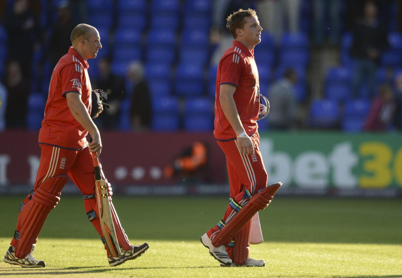 England's Jos Buttler (R) and James Tredwell leave the field after winning the fourth one-day international against Australia at Sophia Gardens in Cardiff, Wales September 14, 2013. REUTERS/Philip Brown (BRITAIN - Tags: SPORT CRICKET)