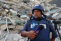 An Al Jazeera journalist stands before the rubble of the Jala Tower, which was housing international press offices, following an Israeli airstrike in the Gaza Strip on May 15