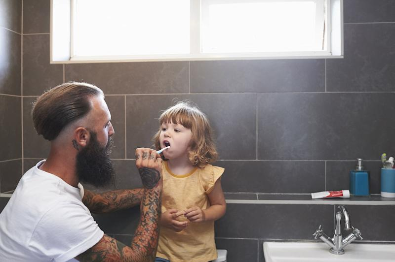 Daughter stands on WC so that Dad can brush her teeth