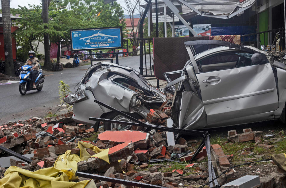 A motorist rides past the wreckage of a car damaged in an earthquake in Mamuju, West Sulawesi, Indonesia, Saturday, Jan. 16, 2021. Damaged roads and bridges, power blackouts and lack of heavy equipment on Saturday hampered Indonesia's rescuers after a strong and shallow earthquake left a number of people dead and injured on Sulawesi island. (AP Photo/Yusuf Wahil)