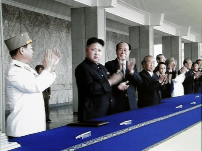 In this image made from KRT video, North Korean leader Kim Jong Un, second from left, applauds while attending a massive celebration marking the 100th birthday of national founder Kim Il Sung, Sunday, April 15, 2012, at Kim Il Sung Square, in Pyongyang, North Korea. Kim, spoke publicly for the first time Sunday, in a speech praising his grandfather, as tens of thousands gathered in Pyongyang's main square for meticulously choreographed festivities that came two days after a failed rocket launch. (AP Photo/KRT via AP video)