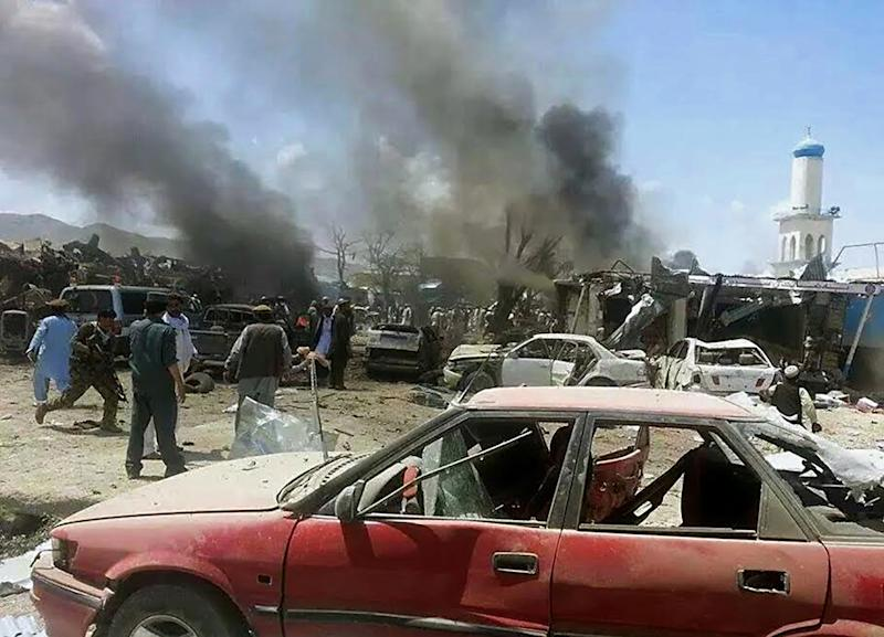 Afghan security personnel are pictured near mangled cars at the scene of a suicide attack at a busy market in Urgun district, Paktika province on July 15, 2014