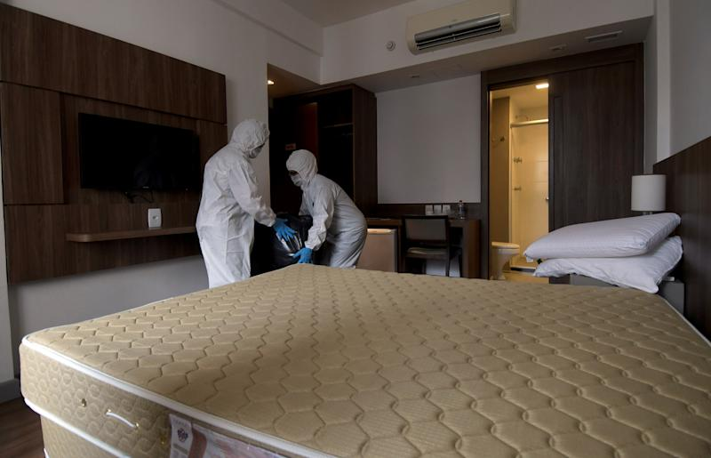 Employees of Vivenzo Hotel wearing protective suits, remove the linen from a room, amid the coronavirus disease (COVID-19) outbreak, in Belo Horizonte, Brazil, April 7, 2020. REUTERS/Washington Alves