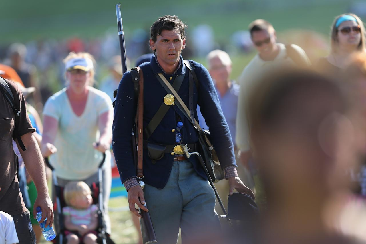 GETTYSBURG, PA - JUNE 29: A Union Civil War re-enactor walks with spectators after taking part in a three-day Battle of Gettysburg re-enactment on June 29, 2013 in Gettysburg, Pennsylvania. Some 8,000 re-enactors from the Blue Gray Alliance are participating in events marking the 150th anniversary of the July 1-3, 1863 Battle of Gettysburg. General Robert E. Lee's Army of Northern Virginia was defeated on the third day of the battle, considered the turning point in the American Civil War and a watershed moment in the nation's history. Union and Confederate armies suffered a combined total of some 46,000-51,000 casualties over three days, the highest of any battle the four-year war. (Photo by John Moore/Getty Images)