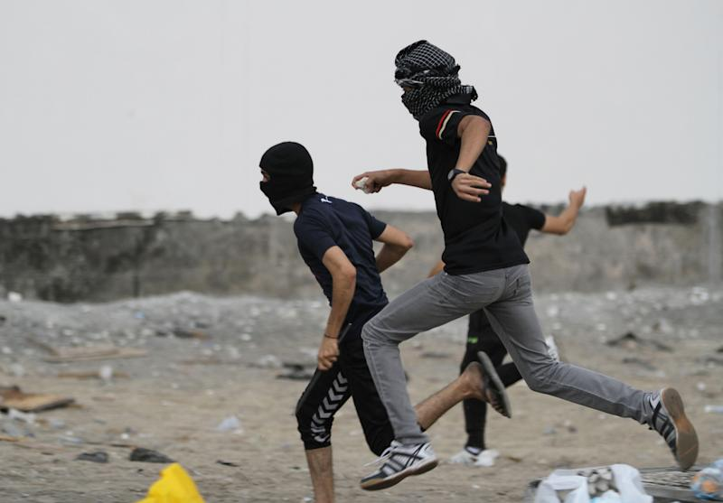 Bahraini youths run from riot police firing tear gas during clashes in the village of Diraz, Bahrain, on Thursday, April 18, 2013. Organizers of Bahrain's Formula One Grand Prix, to be held Sunday, said Thursday that sporadic protests against the race and violent unrest across the Gulf nation do not pose a threat to the premier international event in the kingdom. (AP Photo/Hasan Jamali)