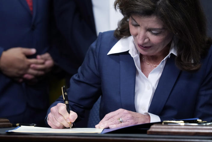 """New York Gov. Kathy Hochul signs the """"Less is More"""" law, during ceremonies in the governor's office, in New York, Friday, Sept. 17, 2021. New Yorkers will be able to avoid jail time for most nonviolent parole violations under a new law that will take effect in March, and largely eliminates New York's practice of incarcerating people for technical parole violations. (AP Photo/Richard Drew)"""