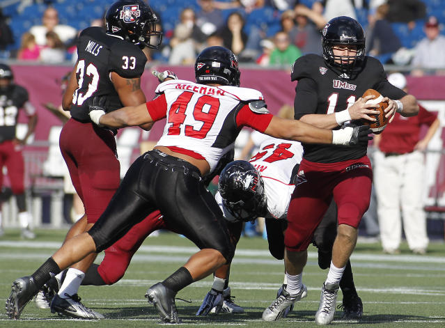 Massachusetts quarterback Mike Wegzyn (11) is tackled by Northern Illinois defensive end Jason Meehan (49) during the second half of an NCAA football game in Foxborough, Mass., Saturday, Nov. 2, 2013. Northern Illinois defeated Massachusetts, 63-19. (AP Photo/Stew Milne)