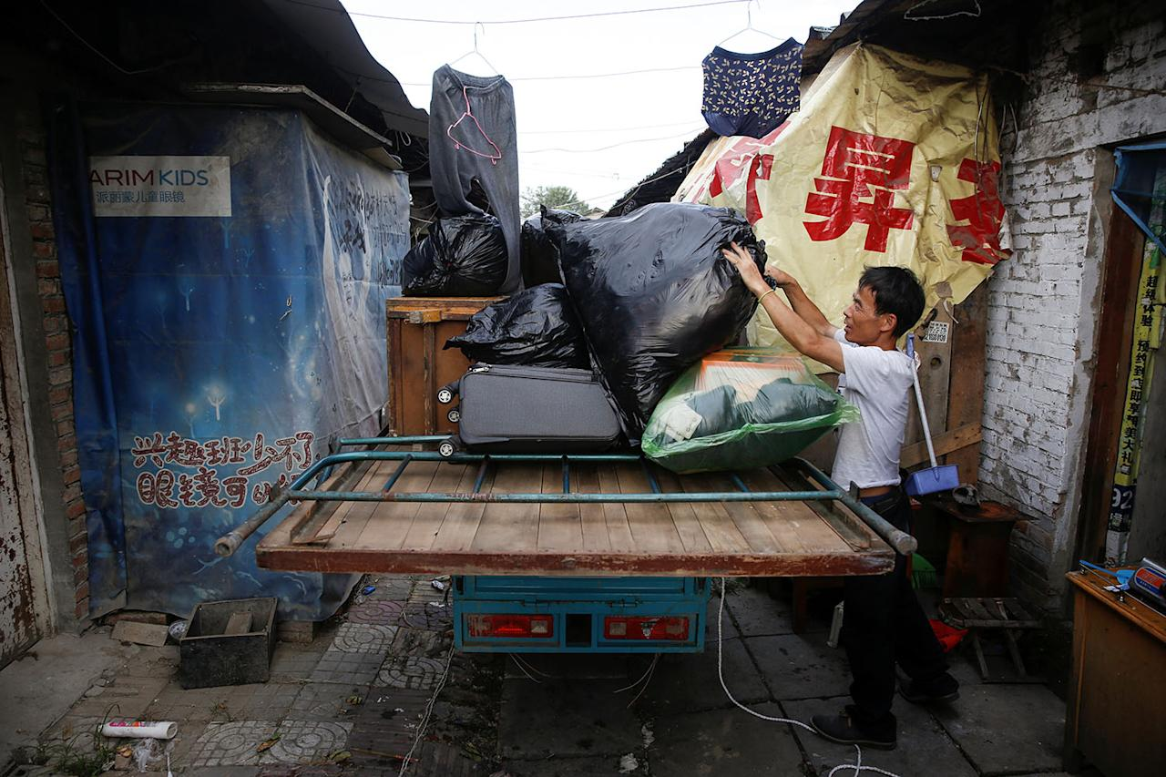 <p>A man loads his belongings onto the flatbed of a tricycle as he moves out of his unit in a cluster of migrant dwellings that is slated for demolition at Dongsanqi village in the outskirts of Beijing, China, August 4, 2017. (Photo: Thomas Peter/Reuters) </p>