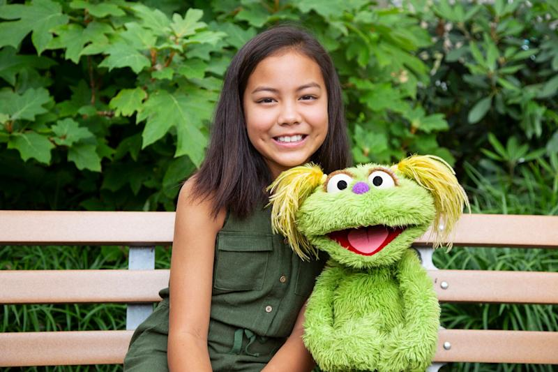 Salia Woodbury, 10, whose parents are in recovery, with Sesame Street character Karli. Together they are addressing the issue of addiction