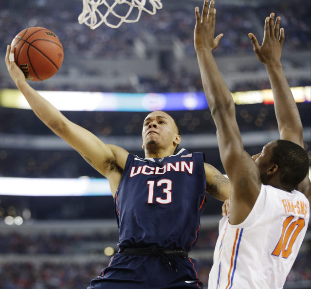 Connecticut guard Shabazz Napier (13) shoots as Florida forward Dorian Finney-Smith (10) defends during the first half of the NCAA Final Four tournament college basketball semifinal game Saturday, April 5, 2014, in Arlington, Texas. (AP Photo/David J. Phillip)