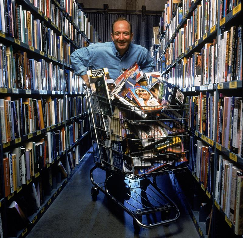 Retrato del empresario estadounidense y CEO de Amazon.com Jeff Bezos posa en un pasillo de estanterías con un carrito de compras lleno de libros y discos compactos, Seattle, Washington, septiembre de 1998. (Foto de Rex Rystedt / The LIFE Images Collection a través de Getty Images / Getty Imágenes)