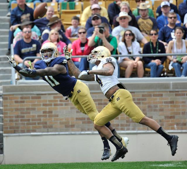 Notre Dame wide receiver Justin Brent reaches for a pass as safety Eilar Hardy defends during the second half of Notre Dame's spring NCAA college football game Saturday April 12, 2014 in South Bend, Ind. The Blue Gold game marks the end of spring football practice. (AP Photo/Joe Raymond)