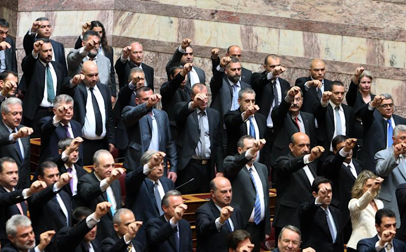 Members of parliament from the extreme right-wing Golden Dawn party, intermingled with other new lawmakers as they are sworn in during a ceremony at the Greek parliament in Athens, Thursday, May 17, 2012. Among the deputies to take their seats for a day are 21 from the Golden Dawn, which rejects the neo-Nazi label. It campaigned on pledges to rid Greece of immigrants and clean up neighborhoods. (AP Photo/Thanassis Stavrakis)
