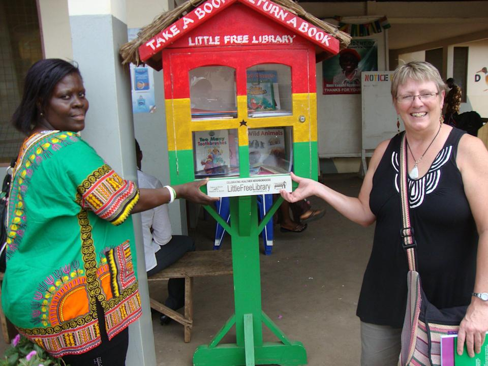 """In this Nov. 17, 2012 photo provided by Kathy Stutzman, Stutzman, right, and Antoinette Ashong, left, the head mistress of a girls' school in Accra, Ghana pose by a """"Little Free Library"""" in Accra. Ashong led an effort that has put up more than 50 little libraries in Ghana. (AP Photo/Kathy Stutzman)"""