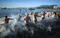 Participants run into English Bay during the 95th annual New Year's Day Polar Bear Swim in Vancouver, British Columbia January 1, 2015. REUTERS/Ben Nelms (CANADA - Tags: SOCIETY ENVIRONMENT ANNIVERSARY)