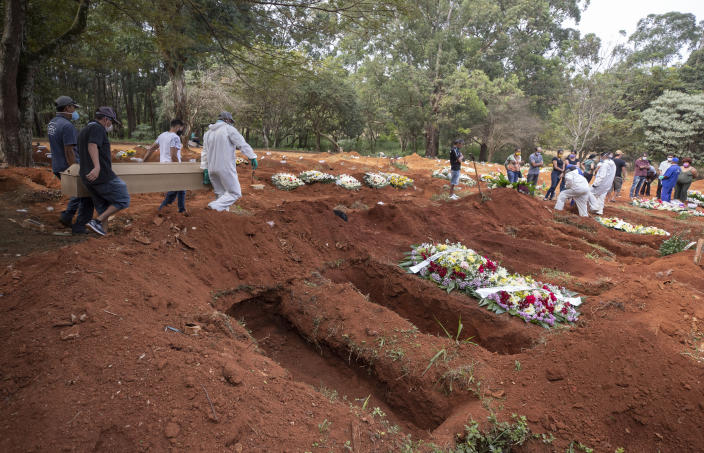 Cemetery workers in protective clothing carry the coffin containing the remains of a person suspected to have died of COVID-19 disease, at the Vila Formosa cemetery in Sao Paulo, Brazil, Thursday, April 30, 2020. (AP Photo/Andre Penner)