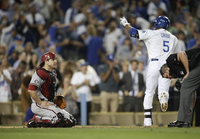 Arizona Diamondbacks catcher Miguel Montero, left, kneels near home plate as Los Angeles Dodgers' Juan Uribe, right, celebrates his solo home run during the third inning a baseball game on Monday, Sept. 9, 2013, in Los Angeles. (AP Photo/Jae C. Hong)
