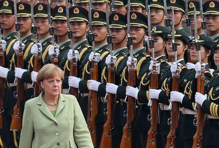 Germany's Chancellor Angela Merkel reviews an honour guard during a welcoming ceremony outside the Great Hall of the People in Beijing