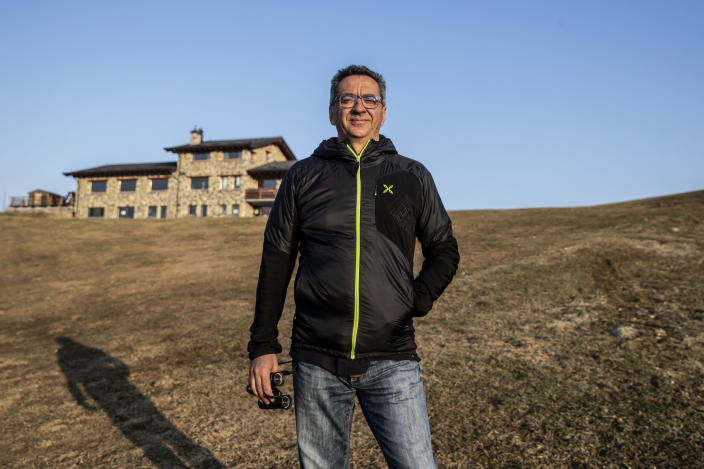 In this image take on Thursday, April 23, 2020 Lorenzo Pasinetti, 53, poses for a portrait in front of his chalet 'Baita Termen', at Monte Pora, near Bergamo, northern Italy. His chalet has a restaurant, a pizzeria a cafe' and an outdoor barbeque, catering for some 2000 people a day in the winter a day and 300 in the summer. After Italy's national lockdown since March 8, he calculated a loss of about 60% compared to the year before. During the restriction measures he stayed open to provide some 10 families living on the mountain with their groceries. (AP Photo/Luca Bruno)