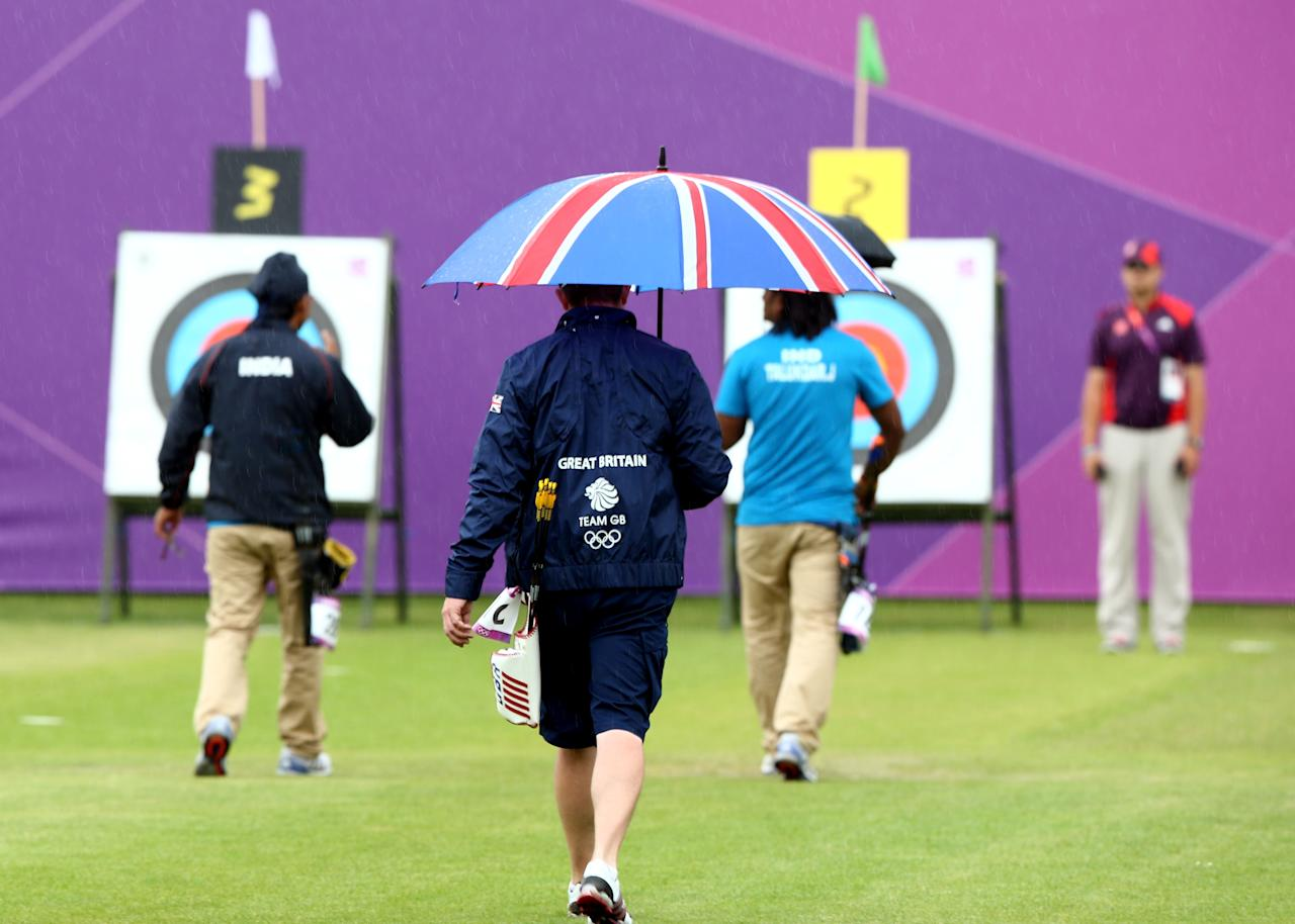 LONDON, ENGLAND - JULY 27:  An archer walks to the targets under an umbrella during an Archery practise session ahead of the London 2012 Olympic Games at the Lord's Cricket Ground on July 27, 2012 in London, England.  (Photo by Paul Gilham/Getty Images)