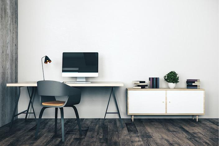 A simple home office space inside a sparse living area.