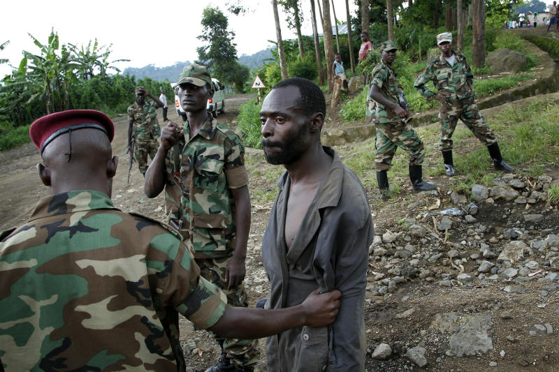Congolese M23 rebel fighters detain a man they suspect to be an FDLR (Force Democratique de Liberation du Rwanda) rebel returning from an incursion into Rwanda Near Kibumba, north of Goma Tuesday Nov. 27, 2012. Speaking in Goma , M23 president Jean Marie Runiga said the rebels will not leave the city of 1 million which they seized a week ago. Rwanda military spokesman confirmed FDLR attacked Rwandan positions on Tuesday, which they repulsed and send back to Congo. (AP Photo / Jerome Delay)