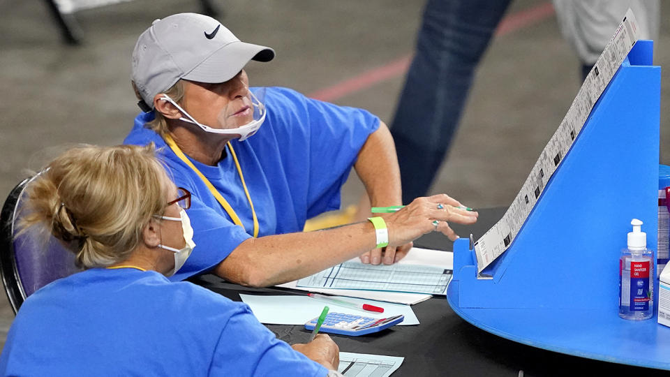 Maricopa County ballots cast in the 2020 general election are examined and recounted by contractors working for Florida-based company, Cyber Ninjas, Thursday, May 6, 2021 at Veterans Memorial Coliseum in Phoenix. (Matt York/Pool via AP)