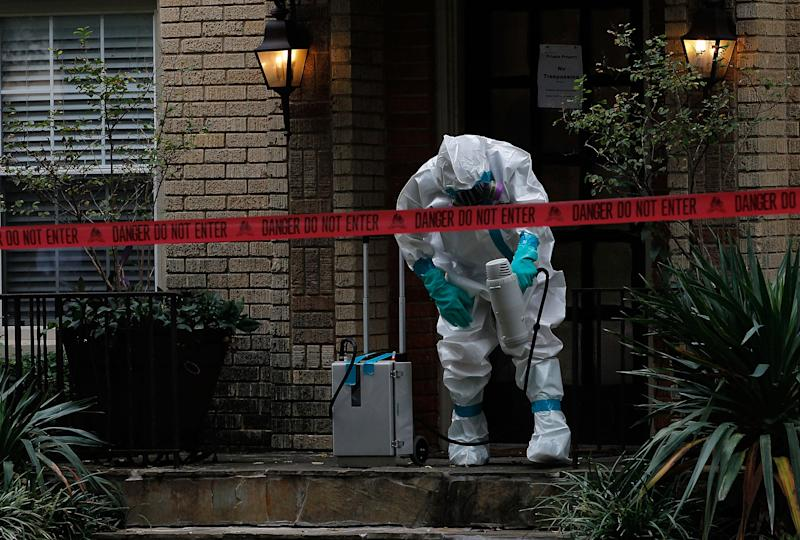 A hazmat worker sprays the front porch of an apartment where a second person diagnosed with the Ebola virus lives, on October 12, 2014 in Dallas, Texas (AFP Photo/Mike Stone)