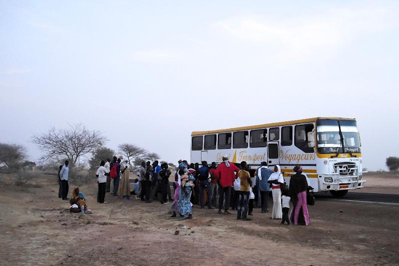 A bus carrying displaced people from the Diffa region of Niger, fleeing fighting between army and Boko Haram on the border between Niger and Nigeria are checked by police on the outskirts of Zinder on February 13, 2014 (AFP Photo/Robert Leslie)