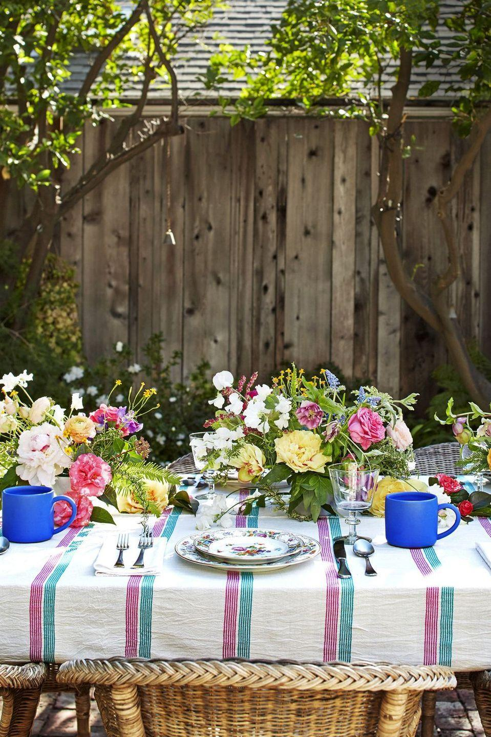 """<p>If you're hosting Easter brunch outside, opt for a wild, eclectic flower arrangement that blends in with the surrounding environment. Here, designer Heather Taylor recreated the motif on her great-grandmother's plates for a <a href=""""https://www.housebeautiful.com/entertaining/table-decor/a8163/tablescape-heather-taylor/"""" rel=""""nofollow noopener"""" target=""""_blank"""" data-ylk=""""slk:garden party"""" class=""""link rapid-noclick-resp"""">garden party</a>'s bouquets. """"Even if guests don't notice the reference, it's a lovely detail that adds a fun symmetry,"""" she says of the bluebells and marigolds.</p><p><strong><em>Crate & Barrel Speckle Vase, $50</em></strong> <a class=""""link rapid-noclick-resp"""" href=""""https://go.redirectingat.com?id=74968X1596630&url=https%3A%2F%2Fwww.crateandbarrel.com%2Fkinai-large-speckled-vase%2Fs100182&sref=https%3A%2F%2Fwww.housebeautiful.com%2Fentertaining%2Fflower-arrangements%2Fg19409803%2Feaster-flower-arrangements%2F"""" rel=""""nofollow noopener"""" target=""""_blank"""" data-ylk=""""slk:BUY NOW"""">BUY NOW</a></p>"""