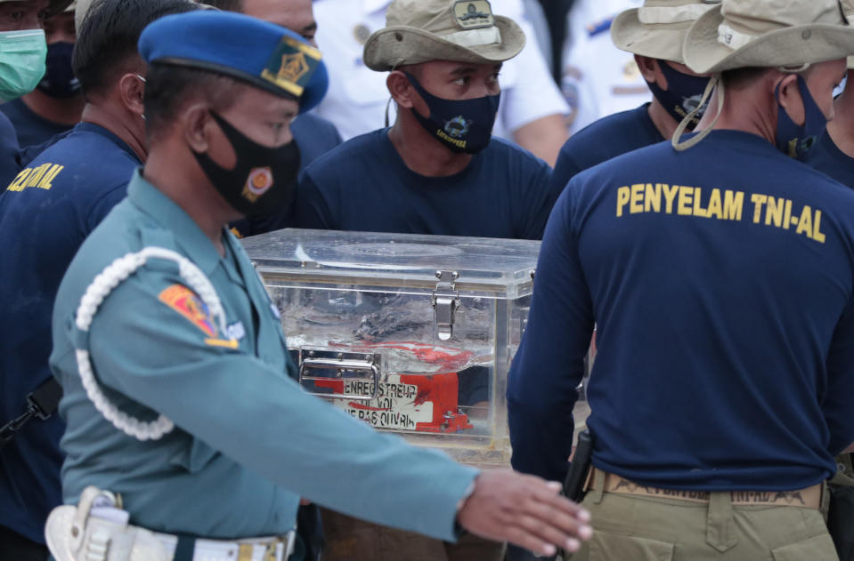 Indonesian Navy personnel carry a box containing the flight data recorder recovered from the crash site of the Sriwijaya Air flight SJ-182 in the Java Sea at Tanjung Priok Port, Tuesday, Jan. 12, 2021. Indonesian navy divers searching the ocean floor on Tuesday recovered the flight data recorder from a Sriwijaya Air jet that crashed into the Java Sea with 62 people on board. (AP Photo/Dita Alangkara)