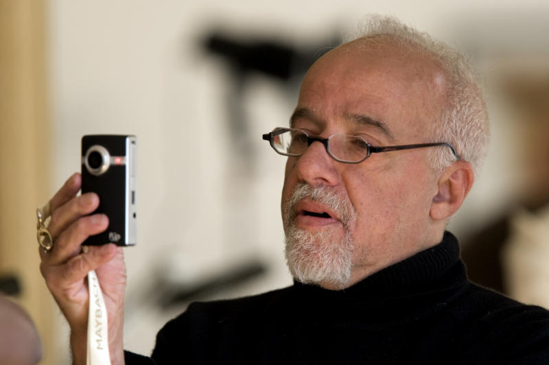 """Brazilian author Paulo Coelho takes a picture during an interview with Reuters at his home in Paris September 18, 2008. Coelho, behind books such as 'The Alchemist' and 'Eleven Minutes', is helping to conjure new literary paradigms through digital platforms. His efforts in the digital realm inspired renowned blogger Jeff Jarvis to label him """"the Googliest author I know"""" - high praise from a journalism professor who is writing a book about Google. REUTERS/Charles Platiau (FRANCE)"""