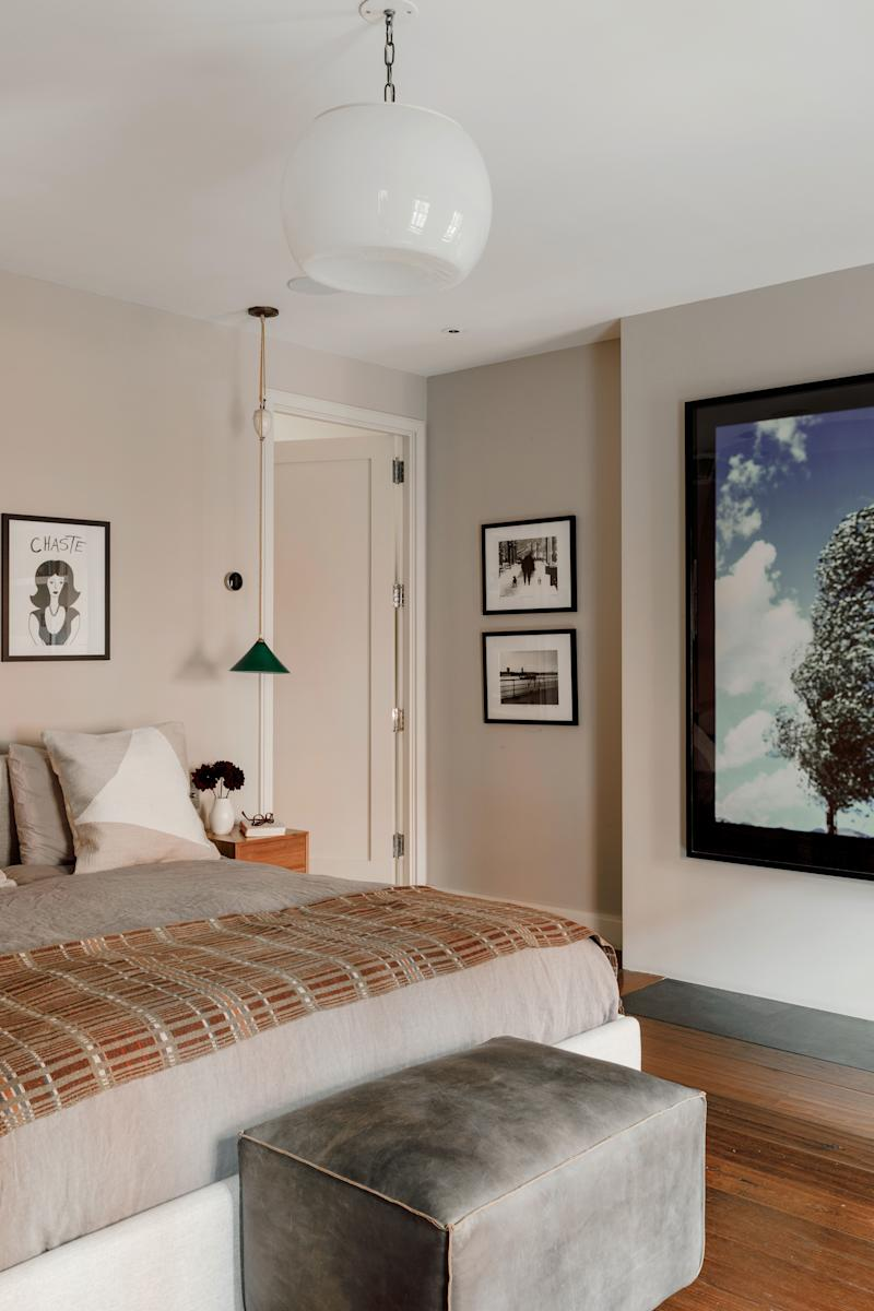 """""""I wanted it to be really simple, and have only special things,"""" says Tierney of the master bedroom. So while—despite Stuno's efforts—it is without unnecessary flourishes like decorative pillows or even a rug, it is filled with meaningful art and her favorite books. The tree image was taken by Kristina Loggia. (""""I don't get tired of looking at it,"""" she says). The 'Chaste' street art was given to her by a friend, and the pair of black-and-white photos are by Reed Rudy."""