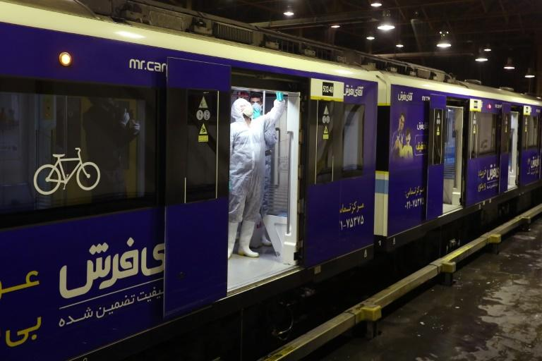 A municipal cleaner disinfects a metro train in Tehran as part of efforts to stem the spread of the coronavirus which has now killed 43 in Iran, according to official figures