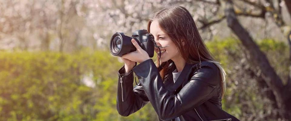 Beautiful female photographer working outdoors