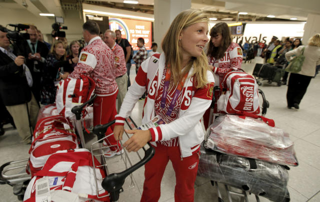 Russian Olympic sailing team athlete Tatiana Bazyuk, centre, and other team members arrive at Heathrow Airport Monday, July 16, 2012, as athletes from all over the world arrive to prepare for the 2012 Summer Olympics. (AP Photo/Charlie Riedel)