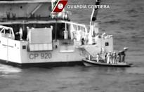 Italian coast guard officers stand on a dinghy beside an Italian coast guard vessel as a massive search and rescue operation is conducted at sea after a boat carrying migrants capsized overnight, in this still image taken from video April 19, 2015. REUTERS/Guardia Costiera/Handout via Reuters