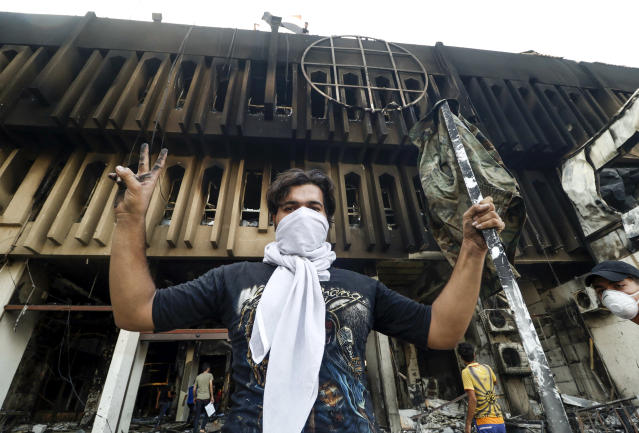 <p>TOPSHOT – Iraqi protesters gather at the burnt-down local government headquarters in the southern city of Basra on September 7, 2018 during demonstrations over poor public services. – Basra has seen a surge in protests since September 4, with demonstrators torching government buildings as well as political party and militia offices, as anger boils over after the hospitalisation of 30,000 people who had drunk polluted water. (Photo by Haidar MOHAMMED ALI / AFP) (Photo credit should read HAIDAR MOHAMMED ALI/AFP/Getty Images) </p>