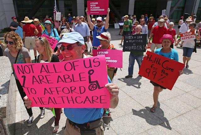 <p>People march during a protest against the Republican bill in the U.S. Senate to replace President Barack Obama's health care law Tuesday, June 27, 2017, in Salt Lake City. Demonstrators with Utah's Disabled Rights Action Committee chanted and carried signs while blocking State Street Tuesday afternoon. Utah protesters criticized Utah Republican Sen. Orrin Hatch for supporting the bill and say it will cut life-saving Medicaid services and other health protections. (Photo: Rick Bowmer/AP) </p>