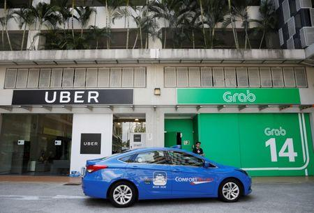FILE PHOTO: A ComfortDelgro taxi passes Uber and Grab offices in Singapore