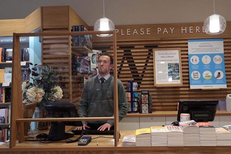 Plexiglass screens are installed behind tills at a London branch of Waterstones: PA