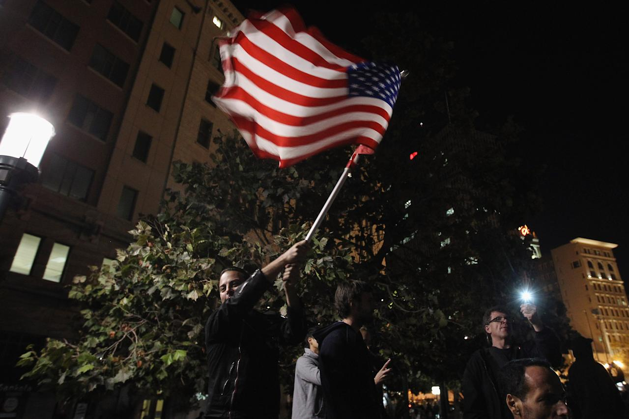 OAKLAND, CA - OCTOBER 26:  A protester waves an American flag at Frank Ogawa Plaza on October 26, 2011 in Oakland, California. Police are allowing protesters back into Frank Ogawa Plaza after the scene of violence there last night, with police firing tear gas into a crowd of hundreds of protesters associated with the Occupy Oakland movement.  (Photo by Justin Sullivan/Getty Images)
