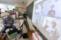 Erick DiVito demonstrates the clarinet as he teaches a remote music class during the coronavirus outbreak at the Osborn School, Tuesday, Oct. 6, 2020, in Rye, N.Y. (AP Photo/Mary Altaffer)